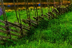 Old wood pole fence from on rural grass meadow. Typical medieval style of fence used in farming.