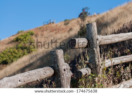 old wood railing on mountain and blue sky