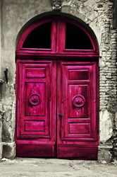 Old wood red door with damaged brick wall