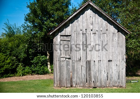 Old wood shack or cabin in the woods against a beautiful bright blue sky