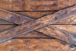 Old wood surface with criss-cross details. Brown planks of aged textured board material with cracked varnish. Part of a rustic fence or antique door close-up.