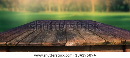 old wood table in field with green blur background use for outdoor background