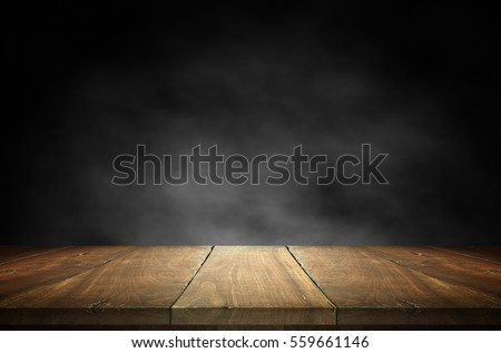 Old wood table top with smoke in the dark background.