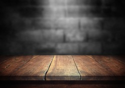 Old wood table with blurred concrete block wall in dark room background.