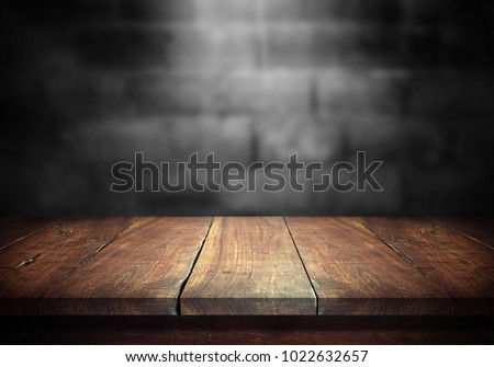 Old wood table with blurred concrete block wall in dark room background. #1022632657