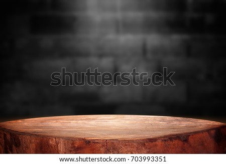 Old wood table with blurred concrete block wall in dark room background. #703993351