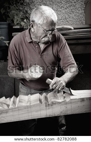 Old woodcarver working with mallet and chiesel, vintage style - stock photo