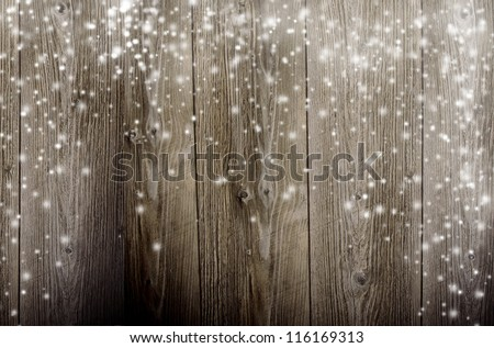 Old wooden background with falling snow flakes - stock photo