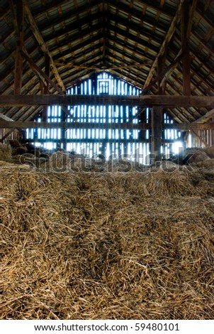 Old wooden barn full of old hay with light shining through the wooden boards.