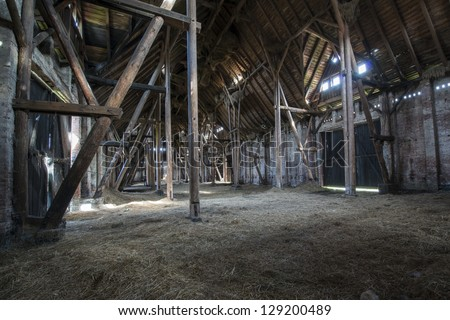 Old wooden barn with light shining through the wooden boards