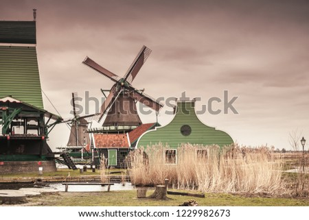 Old wooden barns and windmill on Zaan river coast. Zaanse Schans, popular tourist attractions of the Netherlands. Suburb of Amsterdam. Vintage tonal correction filter