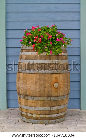old wooden barrel covered with beautiful flowers - home decoration