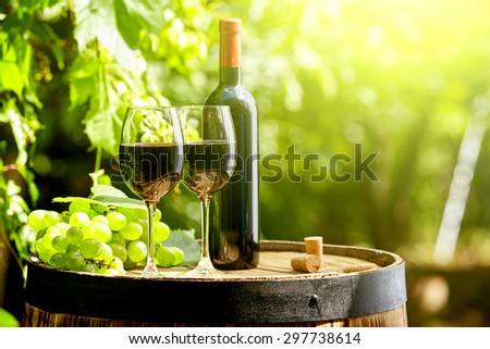 Old wooden barrel with glass of red wine.
