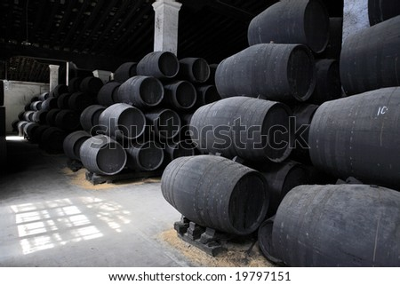 old wooden barrels of sherry in bodega of Spanish town of Jerez de la Frontera