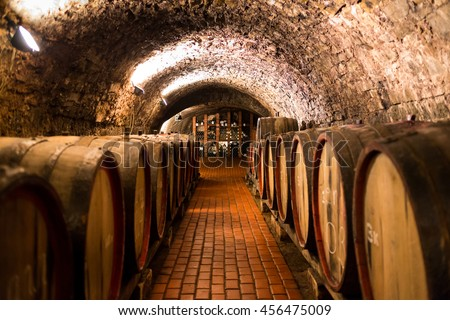 Shutterstock Old wooden barrels with wine in a wine vault, aged traditional wooden vine barrels lined up in cool and dark vine cellar, Italy, Porto, Portugal, France