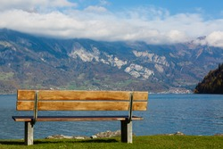Old wooden bench near the coast of a mountain lake.