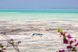 Old wooden boat in tropical sea, low tide, idyll landscape. Tropical seascape, beach by the indian ocean with white sand and turquoise water. Zanzibar island.