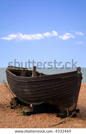 Old wooden boat on a pebble beach.