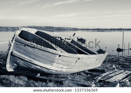 Old wooden boat on the shore of the Mar Piccolo, Italy, calm sea like a lake, in the background the Salento coast, monochromatic interpretation of colors.