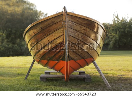Old wooden boat winter storaged on lawn.