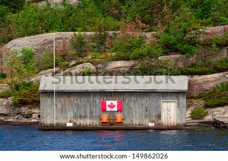 Old wooden boathouse with two Muskoka chairs and Canadian flag