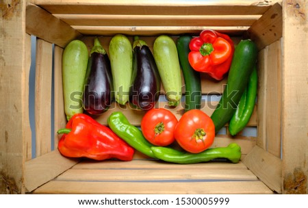 Old wooden box full of freshly harvested fresh vegetables, with red and green peppers, eggplants, zucchini and tomatoes