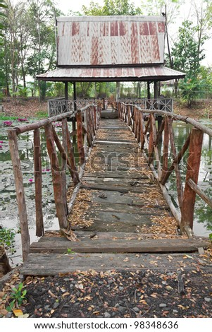 Old wooden bridge. An old wooden bridge that stretches to the hall on the pond.