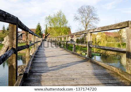 Old wooden bridge for pedestrians in Kostanjevica na Krki, Slovenia, Europe. Stock photo ©