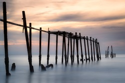Old wooden bridge wreck on beach after storm affect. Landmark of Phang-nga in Thailand