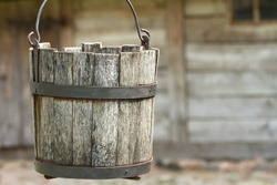 old wooden bucket of water hanging over the well with a wooden building in the background