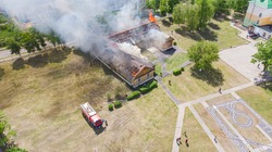 Old wooden building on fire, view from the height. Fire of a building taken from a quadrocopter. Aerial view of a burning building with huge smoke from the burned roof