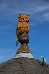 old wooden carved long-eared owl on a rooftop of a historic building