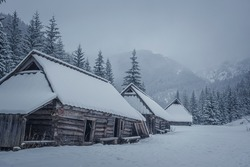 Old wooden chalets in Western Tatras, Poland. Wintry mountain view in Jaworzynka Valley. Foggy morning. Selective focus on the building exterior, blurred background.