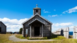 Old wooden chapel front view with blue sky in background