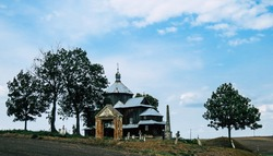 old wooden church orthodox on the Polish-Ukrainian borderland,with the cemetery,  hidden among Polish fields, Polish monument today used as a Catholic church