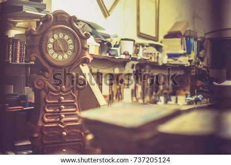 Old wooden clock in a workshop filled with tools, books frames and other things. Horizontal picture. #737205124
