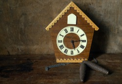 Old wooden clock with a cuckoo and weights on a vintage background