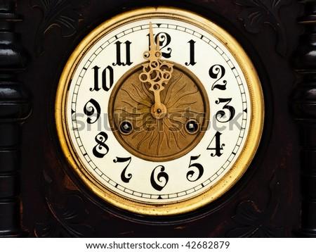 old wooden clock with  golden hands show twelve