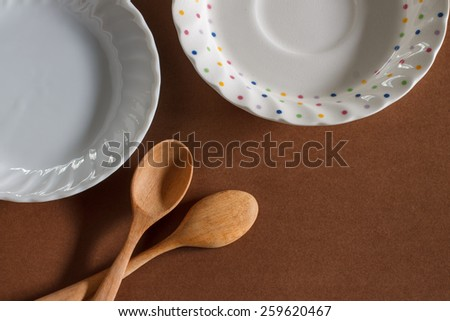 old wooden cooking spoon with small plate put on brown paper background