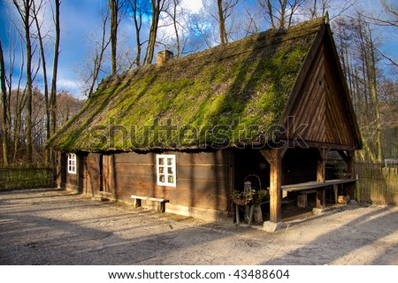Old wooden cottage green grass on the roof. Biskupin Poland.