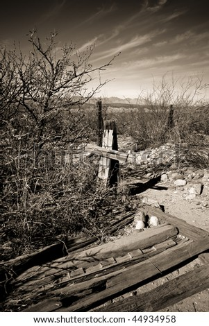 Old wooden cross and fence from Arizona ghost town graveyard with a sepia tone clouded sky and rocks