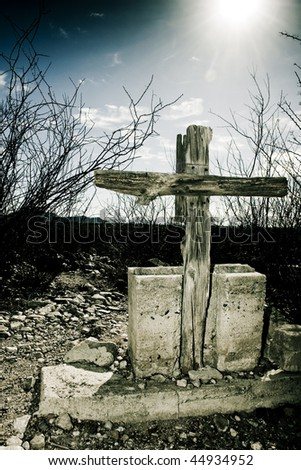 Old wooden cross with cement base from Arizona ghost town graveyard with a clouded sky