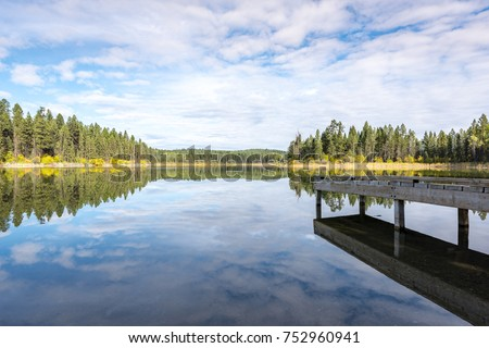 old wooden dock looking out over a motionless Lillian Lake with a mirror like reflection in the morning in British Columbia, Canada #752960941