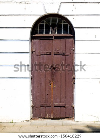 Old wooden door covered with cracked, worn paint