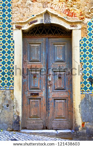 Old wooden door in Portugal. Wall of traditional Portuguese tiles