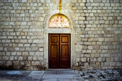 old wooden door in the vintage stone wall
