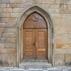 old wooden door in wall - charles bridge, prague