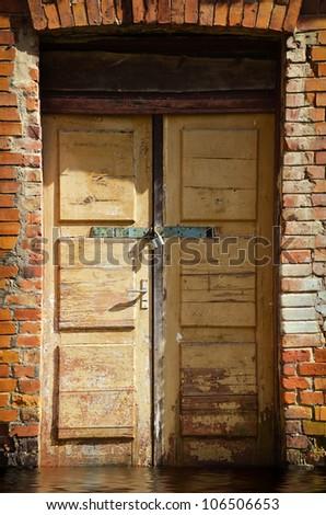 old wooden door locked with a padlock