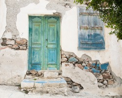 Old wooden door of a shabby demaged house facade or front in blue, green and turquoise.
