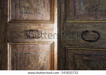 Old wooden door opening with light shining through